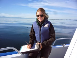 Student Alex Ulmke collecting data on whale from a boat in the Puget Sound