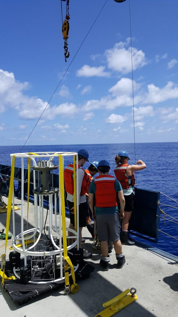 Scientists standing on the side of a ship in the open ocean