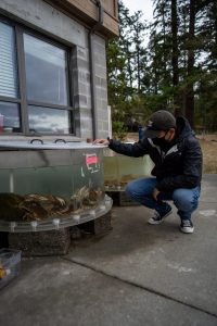 Andy Ni examining his experimental tanks outside of one of the labs.